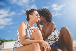 Portrait of two young woman of color whispering to her friend outside