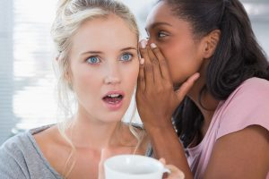 Young woman whispering secret to her shocked friend at home